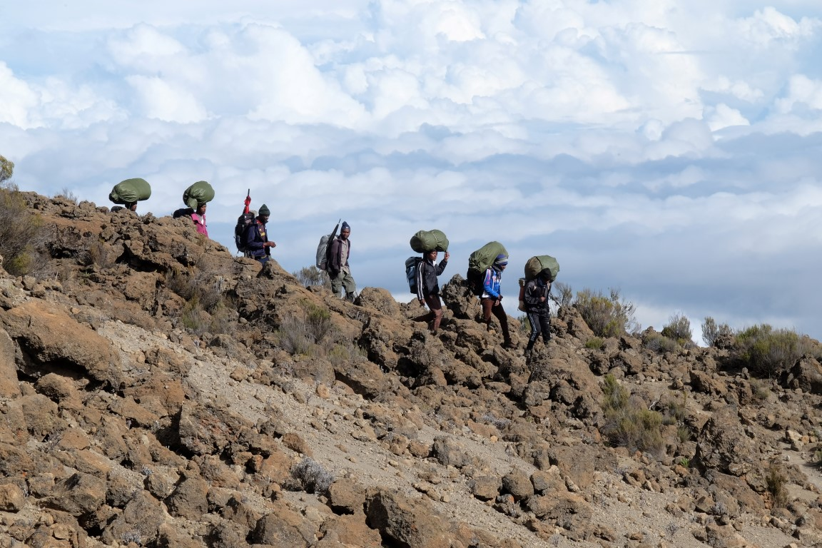 porters climbing in a row with bags