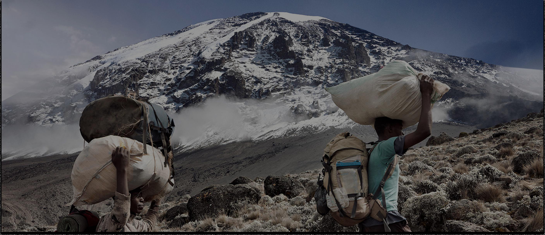 two porters walk up Kilimanjaro
